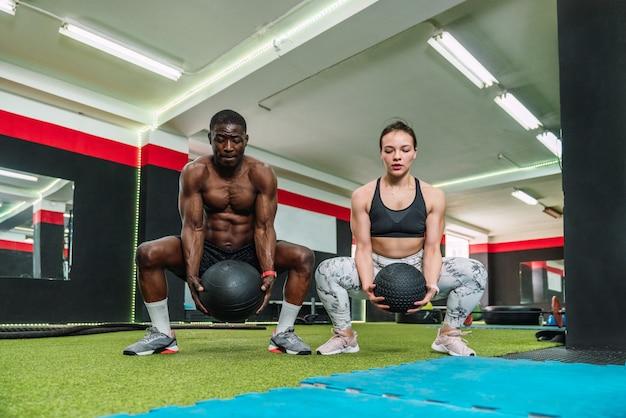 Afrykański chłopiec sportowiec i dziewczyna sportowca rasy kaukaskiej w siłowni robi biceps ramię i ćwiczenia piersiowe z piłką wagi w siłowni. dwóch wielorasowych kulturystów