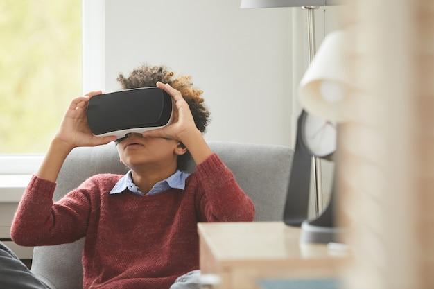 Afrykański chłopiec w wirtualnych okularach siedzi na fotelu i gra w wirtualne gry w domu