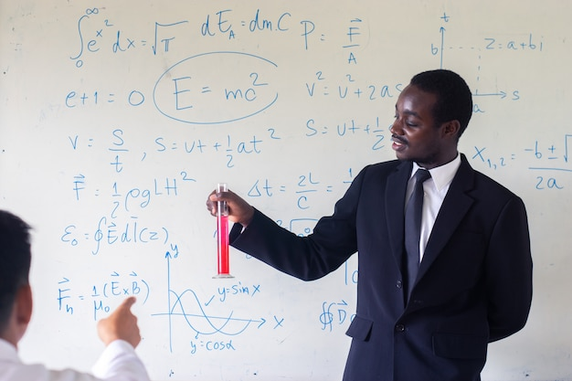 Afrykański cudzoziemski nauczyciel uczy naukę w klasie.