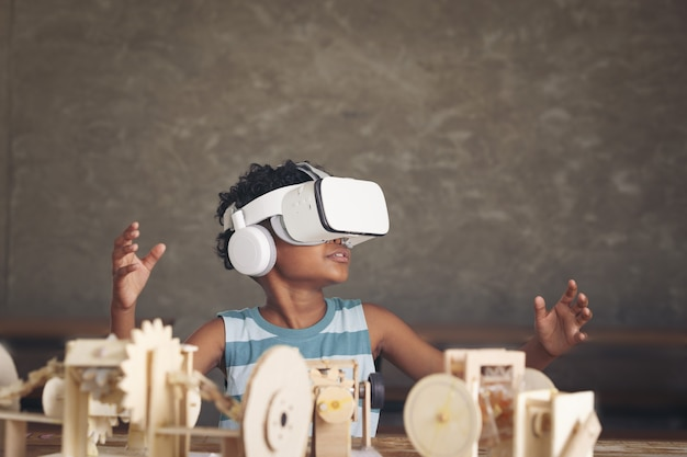 Afrykański czarny chłopiec ubrany w gadżet 3d i mechanizm symulacji drewniany model robota