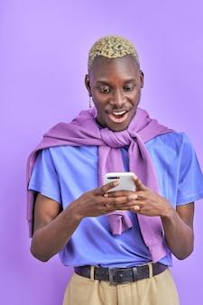 Afrykański czarny model męski z urządzeniem, używa smartfona, rozmawia z przyjacielem, wysyła wiadomość i udostępnia wiadomości, odizolowany na fioletowej przestrzeni, jest w szoku