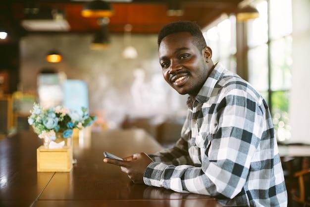 Afrykański człowiek o szczęśliwy czas ze smartfonem w kawiarni