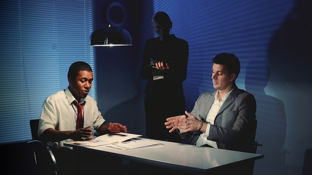 Afrykański detektyw przesłuchuje podejrzanego kaukaskiego w pokoju przesłuchań.
