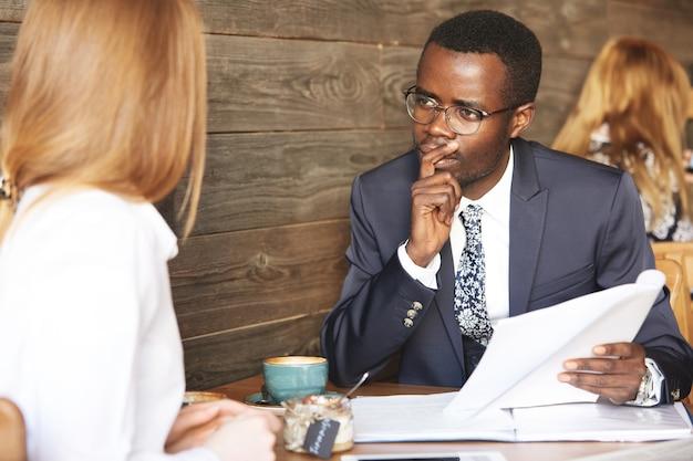 Afrykański dyrektor hr w garniturze przeprowadza rozmowę, przyglądając się kandydatce rasy kaukaskiej