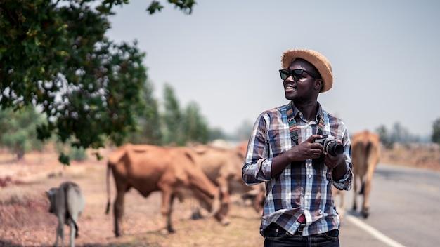 Afrykański fotograf mężczyzna podróżujący na wsi z krowami. styl 16: 9