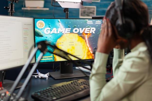 Afrykański gracz e-sportowy przegrywa wirtualny turniej podczas transmisji na żywo obejmującej twarz. profesjonalny gracz strumieniujący gry wideo online z nową grafiką na potężnym komputerze.