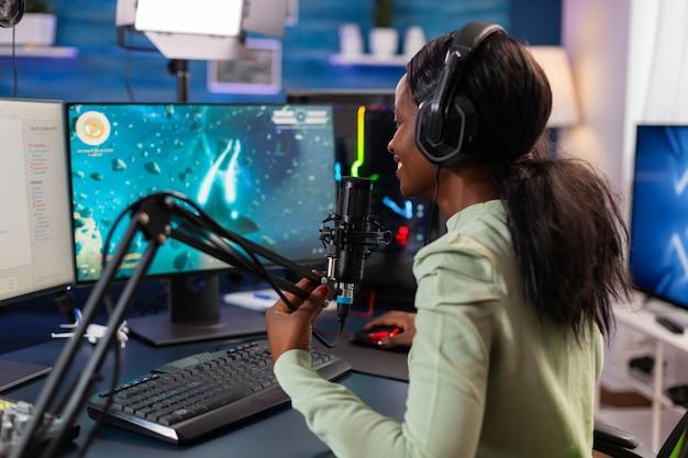 Afrykański gracz e-sportowy rozmawia z drużyną podczas konkursu na żywo w kosmicznej strzelance. streamuj wirusowe gry wideo dla zabawy przy użyciu słuchawek i klawiatury podczas mistrzostw online.