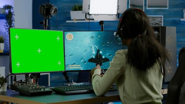Afrykański gracz grający w wirtualną grę wideo na potężnym komputerze, rozmawiający na zielonym ekranie makiety, wyświetlacz chroma key. cyber gracz używający komputera z odizolowanymi strzelankami na komputery stacjonarne z zestawem słuchawkowym
