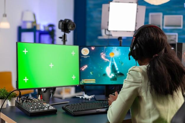 Afrykański gracz strategiczny transmituje strumieniowo za pomocą komputera do e-sportów z kluczem chromatycznym w nocy, rozmawiając z multyplayerami. gracz korzystający z komputera z zielonym ekranem na białym tle stacjonarnych gier wideo w kosmosie.