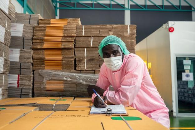 Afrykański kierownik kontroli zapasów w sterylnej odzieży sprawdzający kolejność opakowań kartonowych ułożonych w magazynie w zakładzie przetwórstwa napojów