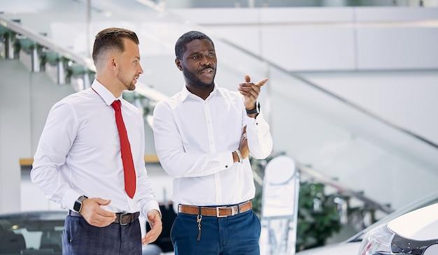 Afrykański klient zadaje pytania dotyczące samochodu, którym jest zainteresowany