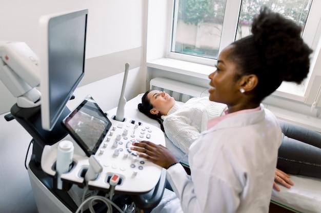 Afrykański kobieta lekarz sonograf skanowania młody brzuch kobiety w ciąży