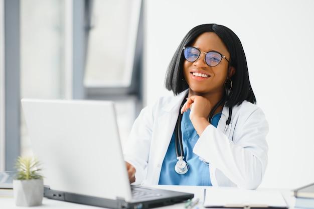 Afrykański lekarz nosi zestaw słuchawkowy skonsultuj się z pacjentem nawiąż połączenie wideo przez kamerę internetową na ekranie laptopa.