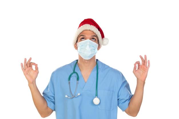 Afrykański lekarz ubrany w świąteczny kapelusz w czasie koronawirusa na białym tle na białym tle
