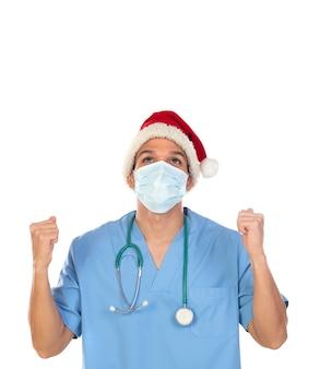 Afrykański lekarz w świątecznej czapce w czasie koronawirusa na białym tle na białej ścianie