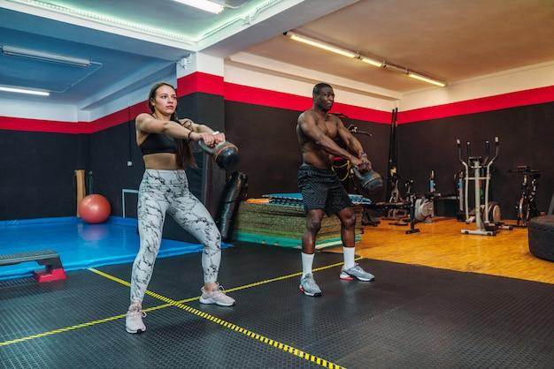 Afrykański lekkoatletka chłopiec i kaukaska dziewczyna lekkoatletka w siłowni robi biceps na ramię i ćwiczenia piersiowe z kettlebells w siłowni. dwóch wielorasowych kulturystów
