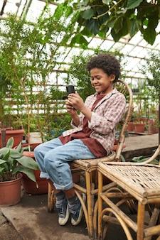 Afrykański mały chłopiec rozmawia online przez telefon komórkowy, odpoczywając na krześle w szklarni
