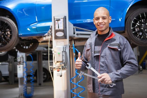 Afrykański męski samochodowy usługowy pracownik naprawia samochody przy jego warsztatem