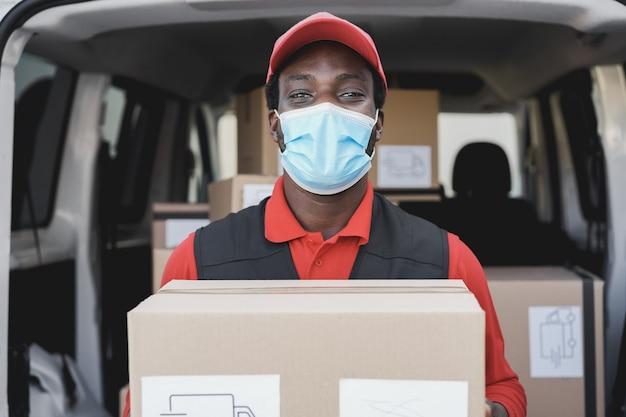 Afrykański mężczyzna dostawy uśmiechnięty podczas noszenia maski bezpieczeństwa