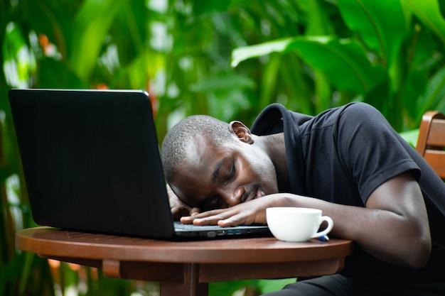 Afrykański mężczyzna dosypianie na laptopie z zieloną naturą.