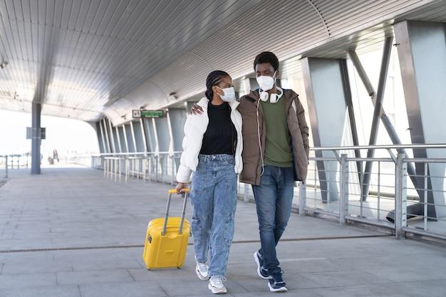 Afrykański mężczyzna i kobieta idą do odlotu samolotu poza lotniskiem w maskach ochronnych