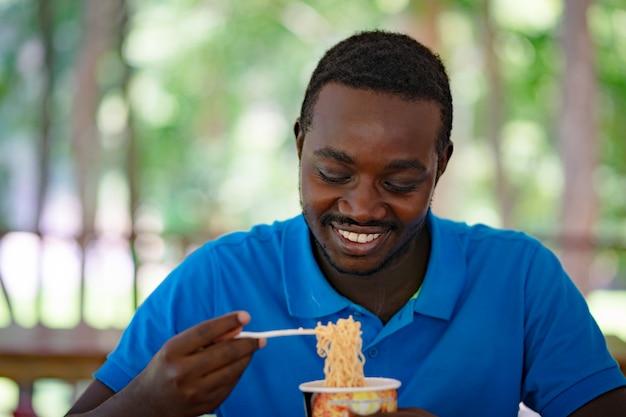 Afrykański mężczyzna je natychmiastową zupę z makaronem na lunch