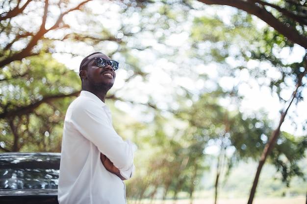 Afrykański mężczyzna jest ubranym białą koszula i okulary przeciwsłonecznych stoi samochodem