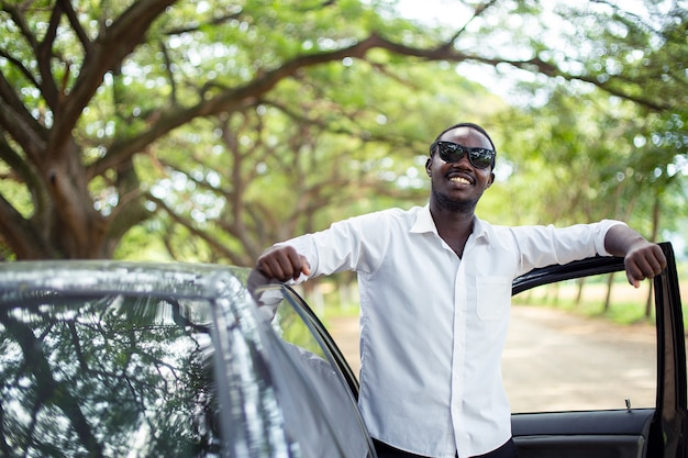 Afrykański mężczyzna jest ubranym białą koszula i okulary przeciwsłonecznych