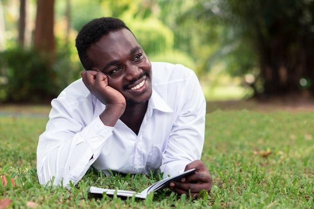 Afrykański mężczyzna kłama na trawie i czyta książkę