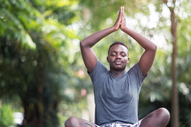 Afrykański mężczyzna medytuje na zielonej trawie w parku
