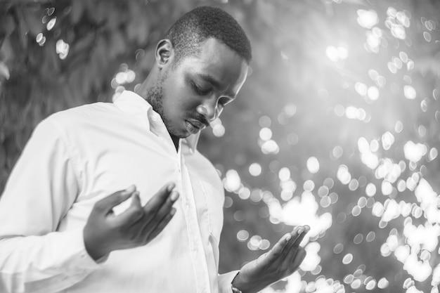 Afrykański mężczyzna modlący się o dziękczynienie bogu z lekkim rozbłyskiem i pięknym bokeh w czarno-białym stylu