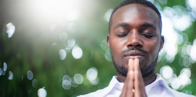 Afrykański mężczyzna modlący się o dzięki bogu z lekkim rozbłyskiem i pięknym bokehem w zielonym tle przyrody
