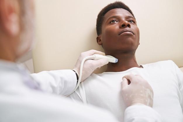 Afrykański mężczyzna na diagnostyce ultrasonograficznej węzłów chłonnych na szyi.