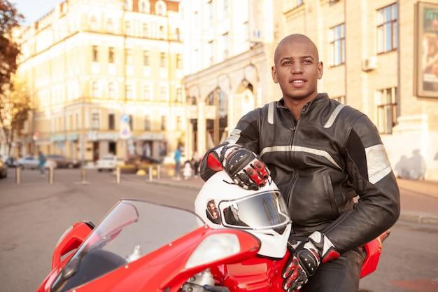 Afrykański mężczyzna na sporta motocyklu w mieście