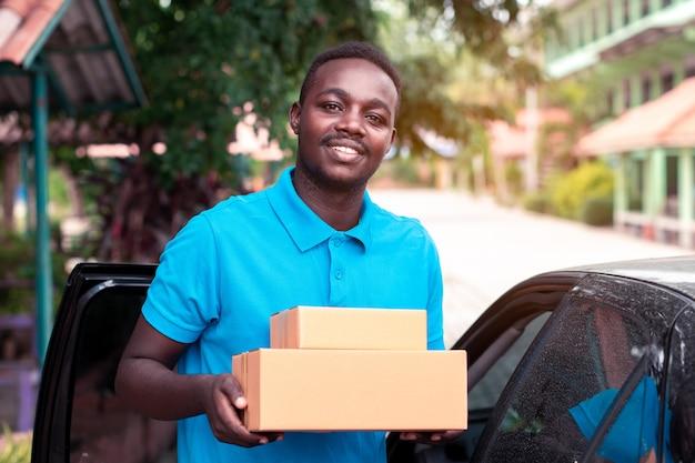 Afrykański mężczyzna niesie pakunek od doręczeniowego samochodu