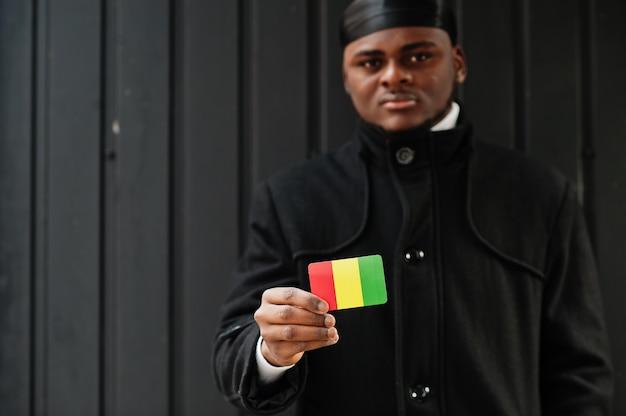 Afrykański mężczyzna nosić czarny durag trzymać flagę gwinei pod ręką na białym tle ciemną ścianę.