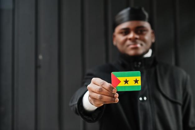 Afrykański mężczyzna nosić czarny durag trzymać flagę wysp świętego tomasza i książęcej pod ręką na białym tle ciemną ścianę.