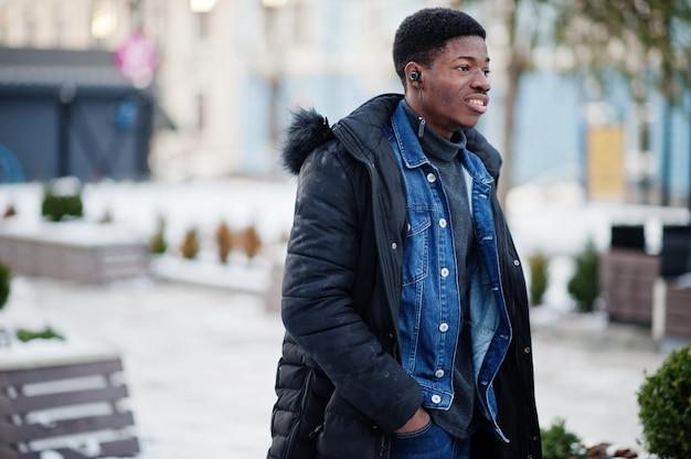 Afrykański mężczyzna nosić kurtkę w chłodne zimowe dni pozował na zewnątrz ze słuchawkami na uszach.