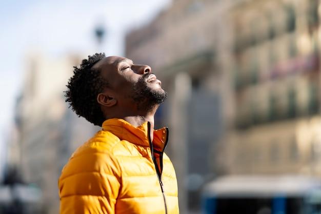 Afrykański mężczyzna oddychający świeżym powietrzem na zewnątrz stojący w mieście