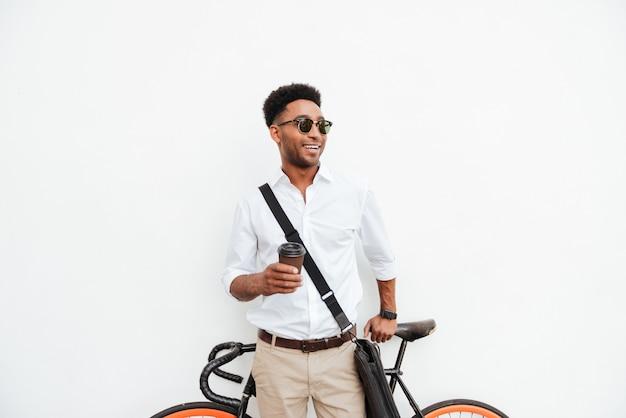 Afrykański mężczyzna pije kawę z bicyklem.