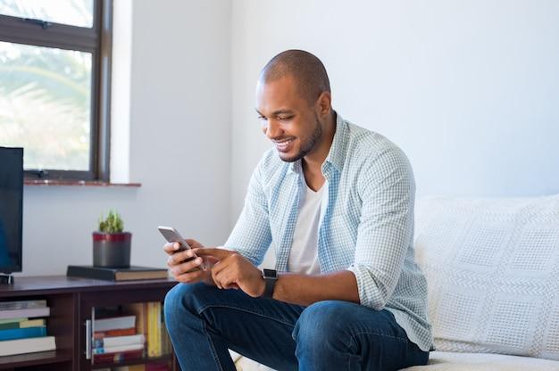 Afrykański mężczyzna pisać na maszynie wiadomość telefon