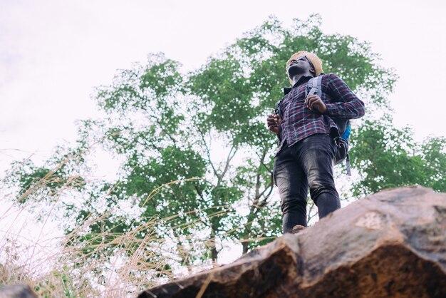 Afrykański mężczyzna podróżnik stojący na szczycie góry iz plecakiem