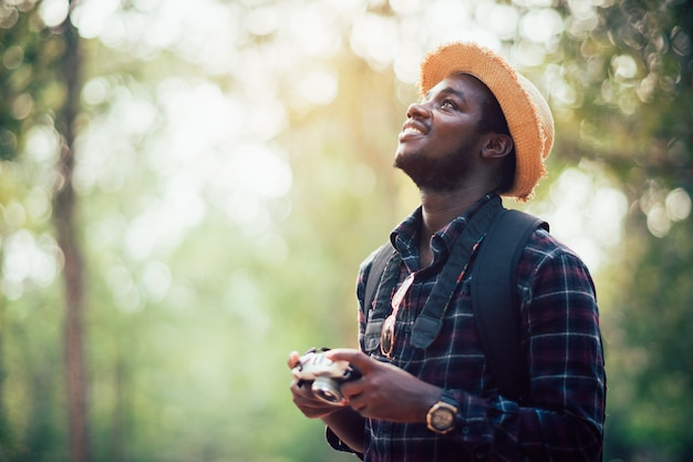 Afrykański mężczyzna podróżnik trzyma ekranową kamerę