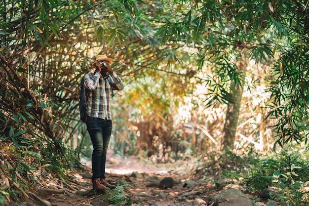 Afrykański mężczyzna podróżnik używa kamerę z plecak pozycją w zielonym naturalnym lesie.