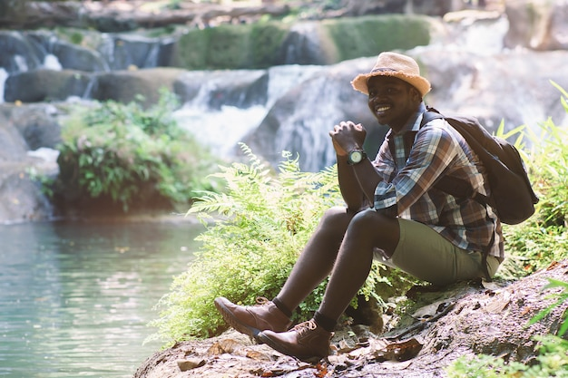 Afrykański mężczyzna podróżnik z plecakiem uśmiechniętym i relaksującym
