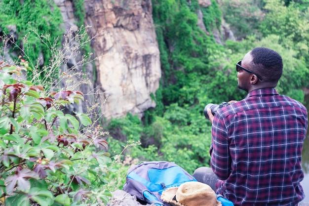 Afrykański mężczyzna podróżnika obsiadanie na falezie i mienia kamera