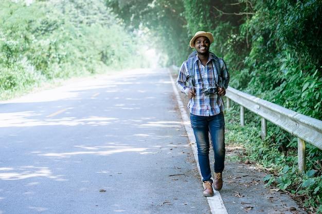 Afrykański mężczyzna podróży przewożenia plecaka odprowadzenie na autostrady drodze