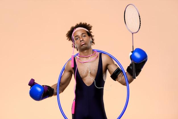 Afrykański mężczyzna pozowanie z rękawice bokserskie, obręcz, skakanka i rakieta