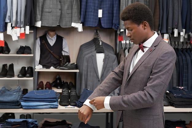 Afrykański mężczyzna próbuje na garnitur w butiku, patrząc na rękaw.