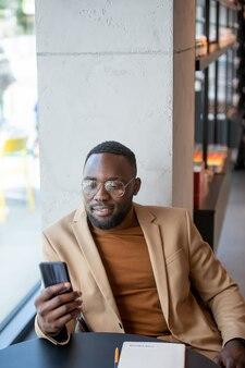 Afrykański mężczyzna przewijający się w smartfonie przy stole w księgarni